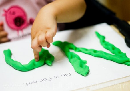 Poking Play Dough letters